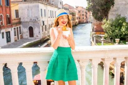 Woman eating food from bowl on bridge over river in Rome