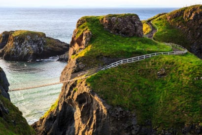 Rope bridge across cliff over the ocean in Ireland