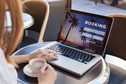 woman booking flights from laptop in coffee shop