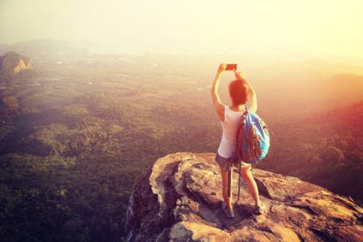woman taking photo of sunset over rolling hills from cliff