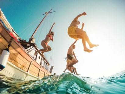 Group jumping into ocean off of boat