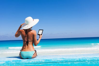 Woman reading from Kindle on the beach