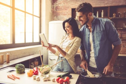 couple looking at recipe as they are making dinner
