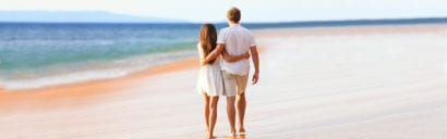 Couple walking along beach in exotic location for honeymoon